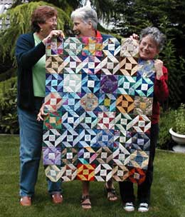 guild members hold the quilt made up of members friendship star blocks
